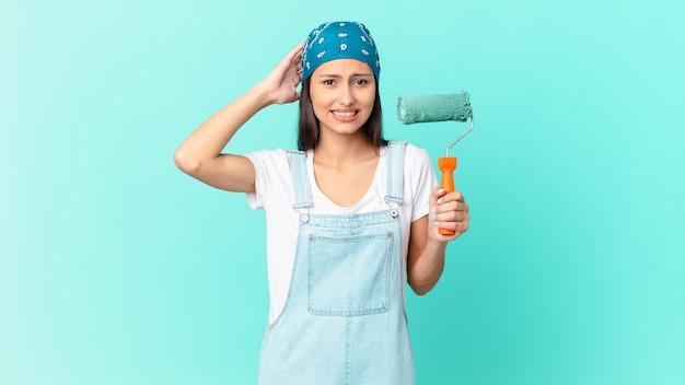 Mooie spaanse vrouw die zich gestrest, angstig of bang voelt, met de handen op het hoofd. schilderij thuis concept