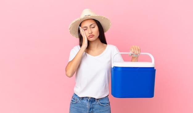 Mooie spaanse vrouw die zich verveeld, gefrustreerd en slaperig voelt na een vermoeiende bezigheid en een draagbare koelkast vasthoudt
