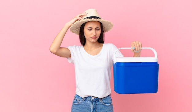 Mooie spaanse vrouw die zich verward en verward voelt, haar hoofd krabt en een draagbare koelkast vasthoudt