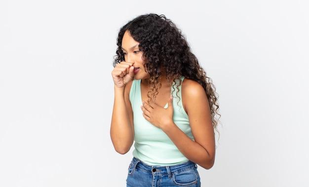 Mooie spaanse vrouw die zich ziek voelt met een zere keel en griepsymptomen, hoest met bedekte mond