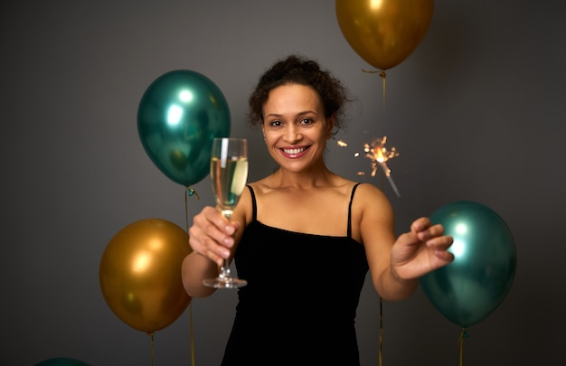 Mooie spaanse vrouw houdt een fluit champagne vast en sterretjes glimlachen met een mooie brede glimlach