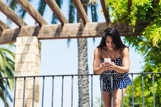Mooie spaanse vrouw in blauwe jurk leunend op hek tijdens het gebruik van een mobiele telefoon