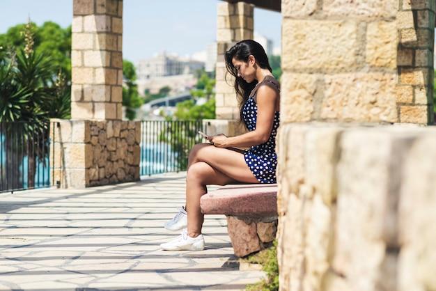 Mooie spaanse vrouw in blauwe jurk zittend op een bankje tijdens het gebruik van een smartphone