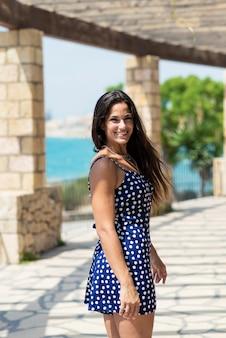 Mooie spaanse vrouw in blauwe kleding die zich in openlucht terwijl het kijken camera bevinden
