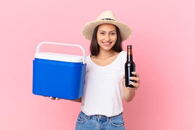 Mooie spaanse vrouw met een draagbare vriezer en een biertje Premium Foto