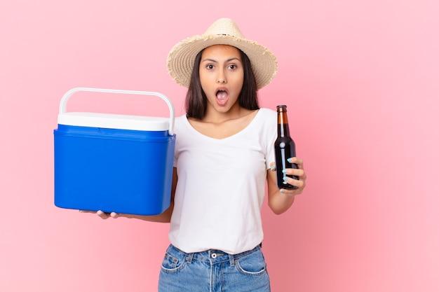 Mooie spaanse vrouw met een draagbare vriezer en een biertje