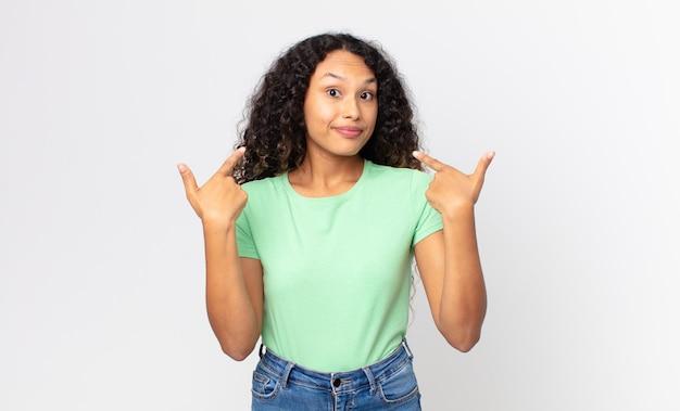 Mooie spaanse vrouw met een slechte houding die er trots en agressief uitziet, naar boven wijst of een grappig teken maakt met handen