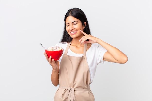 Mooie spaanse vrouw mooie spaanse chef-kokvrouw die vrolijk lacht en dagdroomt of twijfelt en een cornflakeskom vasthoudt