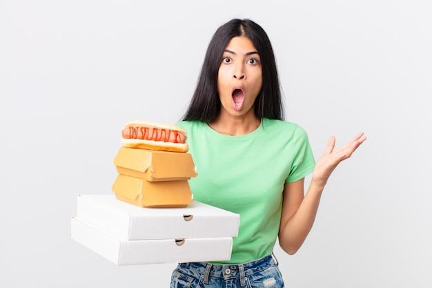 Mooie spaanse vrouw verbaasd, geschokt en verbaasd met een ongelooflijke verrassing en met afhaalmaaltijden voor fastfood