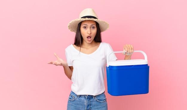 Mooie spaanse vrouw verbaasd, geschokt en verbaasd met een ongelooflijke verrassing en met een draagbare koelkast