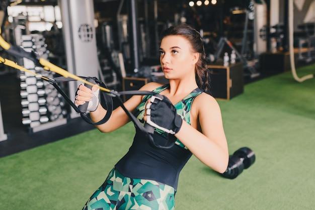 Mooie spiervrouw die oefening met trxsysteem doet. jonge vrouw die met schorsingstrainer uitoefenen bij gymnastiek.