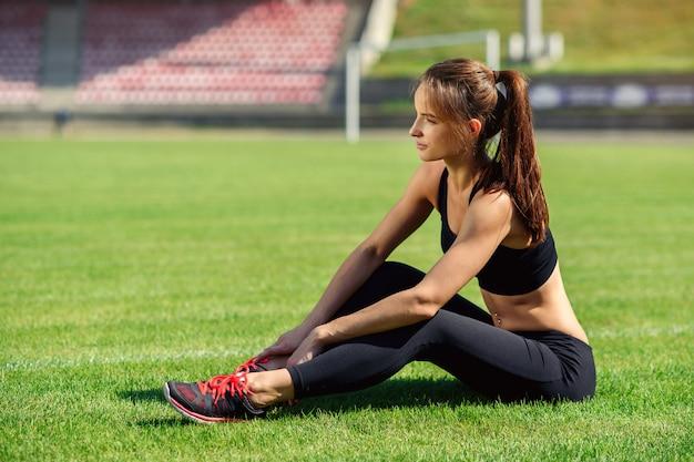 Mooie sportenvrouw in zwarte sportkleding en tennisschoenen die op groen gras rusten