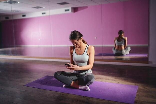 Mooie sportieve brunette met paardenstaart en in sportkleding zittend op de mat met gekruiste benen en bericht aan het typen op smartphone.