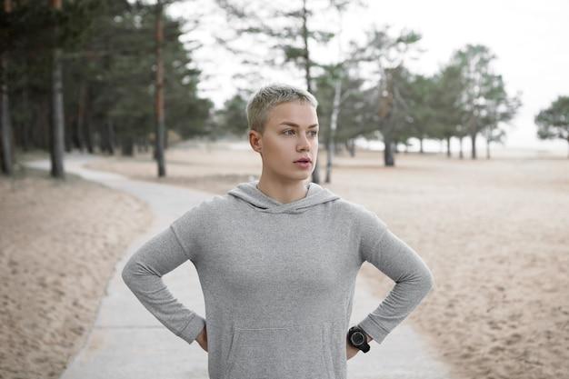 Mooie sportieve jonge kortharige blonde vrouw met vermoeide blik, op adem komen na het hardlopen van de ochtend, hand in hand op haar middel, poseren op verhard pad tegen zandstrand en pijnbomen achtergrond