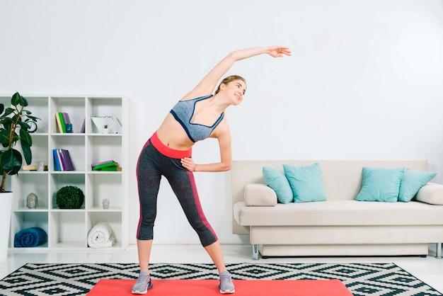 Mooie sportieve jonge vrouw die in de moderne woonkamer uitoefent