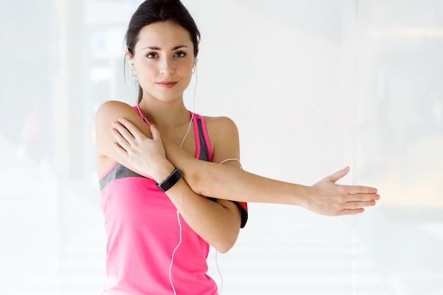 Mooie sportieve jonge vrouw die oefening in de sportschool doet.