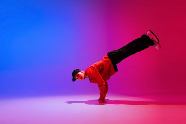 Mooie sportieve jongen hiphop dansen in stijlvolle kleding op kleurrijke gradiëntmuur in danszaal in neonlicht. jeugdcultuur, beweging, stijl en mode, actie. modieus helder portret.