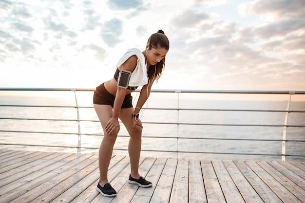 Mooie sportieve meisje opleiding bij zonsopgang boven zee.