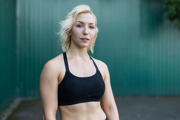 Mooie sportieve vrouw die camera bekijkt
