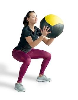 Mooie sportieve vrouw die hurkzit met med bal doet. foto van spiergeschiktheidsmodel dat op witte achtergrond wordt geïsoleerd. fitness en gezonde levensstijl concept