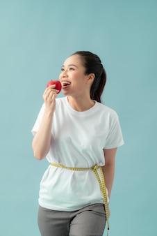 Mooie sportieve vrouw die meetlint gebruikt dat appelfruit eet over blauwe achtergrond
