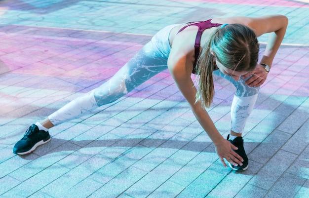 Mooie sportieve vrouw die oefening op de vloer doet