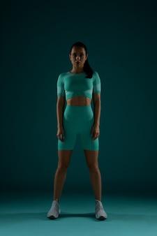 Mooie sportieve vrouw die zich tegen groene achtergrond bevindt