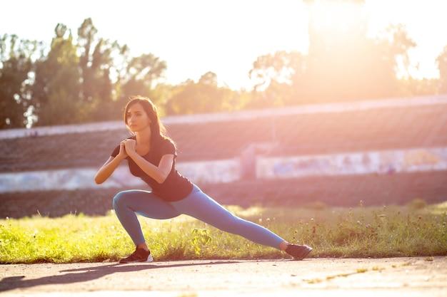 Mooie sportieve vrouw die zich uitstrekt voor de training in het stadion. buiten geschoten met zonnestralen. ruimte voor tekst