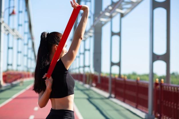Mooie sportieve vrouw doet training met rubberen weerstandsband op een brug. ruimte voor tekst