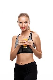 Mooie sportieve vrouw met glas met sap