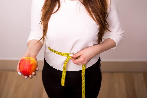 Mooie sportieve vrouw met groene appel en meetlint
