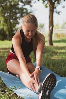 Mooie sportieve vrouw met lang haar die zich uitstrekt in het park voordat ze joggen