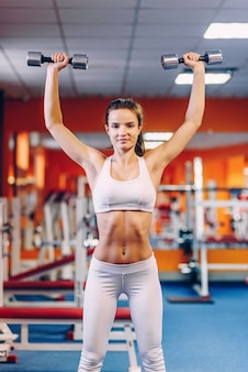 Mooie sportieve vrouw met perfect lichaam die trainingen met domoren in de gymnastiek doen
