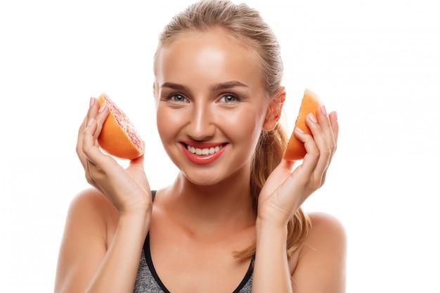 Mooie sportieve vrouw poseren, grapefruit houden