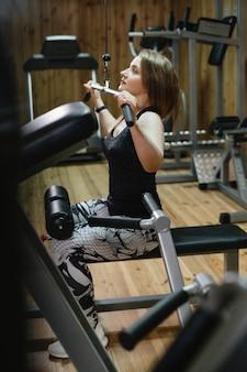 Mooie sportieve vrouw tillen gewicht in sportschool op fitnessapparaat. vrouw powerlifter van middelbare leeftijd met tatoeage. sterk en fit lichaam, gezond levensstijlconcept. vrouw bij 40
