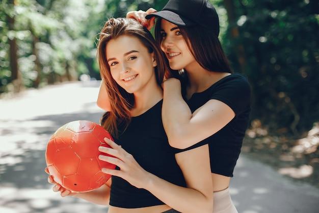 Mooie sportmeisjes in een zomer zonnig park