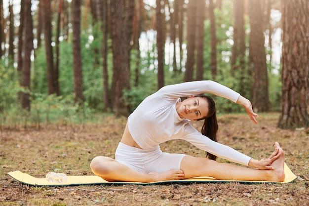 Mooie sportvrouw die in de open lucht traint, op de mat op de grond zit en haar lichaam strekt, witte sportieve top en legging draagt, traint op de natuur in het bos.