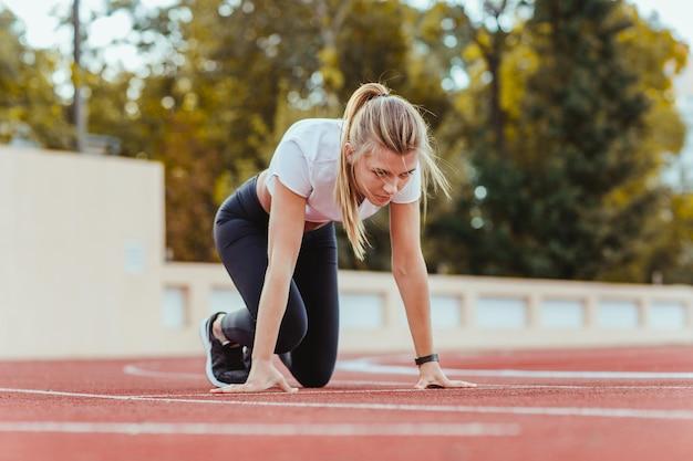 Mooie sportvrouw die zich in startpositie voor het runnen op openluchtstadion bevindt