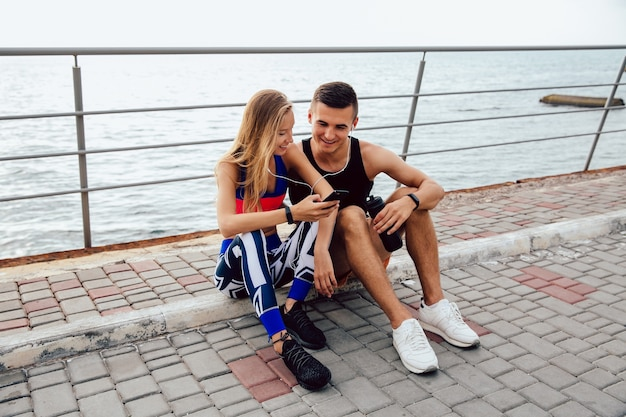 Mooie sportvrouw en knappe sportman die op een grappige video op mobiele telefoon letten