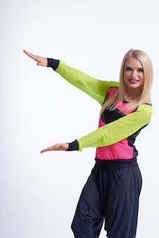 Mooie sportvrouw glimlachend vrolijk wijzend op de copyspace op wit