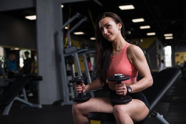 Mooie sportvrouw glimlacht, geniet van trainen met halters, kopieer ruimte