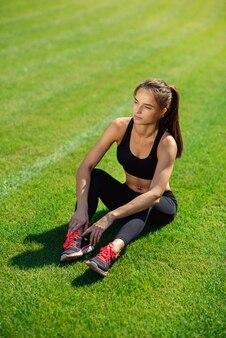 Mooie sportvrouw in zwarte sportkleding en tennisschoenen die op groen gras na intensieve training rusten
