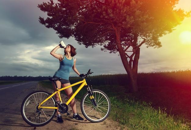 Mooie sportvrouw met fiets drinkwater uit een fles.