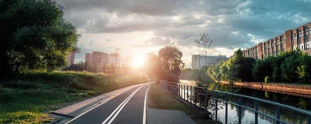Mooie stadszonsondergang, stadsstraat bij zonsondergang in de avond