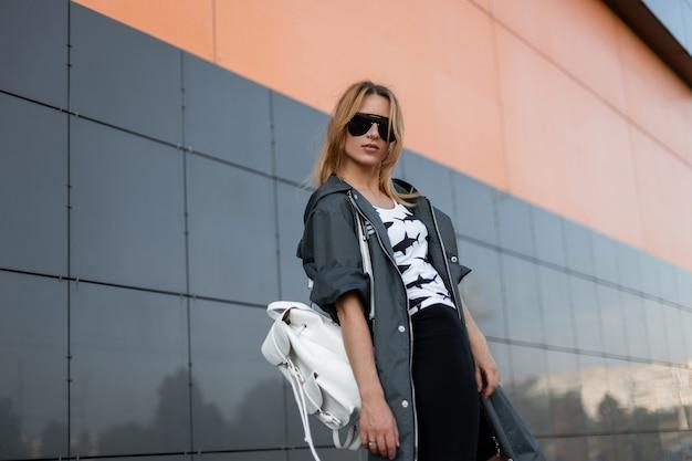 Mooie stedelijke jonge vrouw met rood haar in een stijlvol jasje in trendy zonnebril in een wit t-shirt met een patroon poseren buiten in de buurt van een modern gebouw. mooi meisjesmodel in de stad.