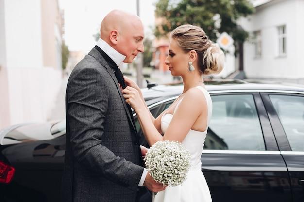 Mooie sterke bruidegom kijkt naar zijn mooie bruid in de buurt van de limousine buiten