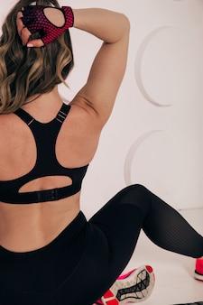 Mooie sterke gespierde vrouw die haar biceps en armspieren buigt. bekijk van achteren om haar gescheurde rug en armen te laten zien.