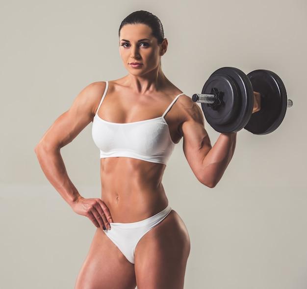 Mooie sterke vrouw in wit ondergoed met halters