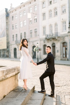 Mooie stijlvolle aziaten paar man en vrouw lopen op de zomer straten van de oude europese stad