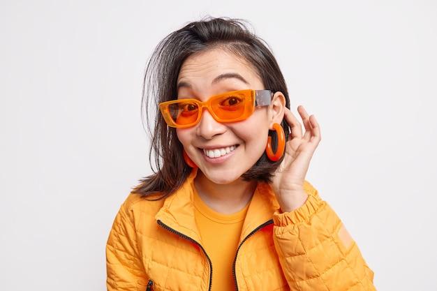 Mooie stijlvolle aziatische tiener ziet er gelukkig glimlacht breed geniet van zonnige lentedag draagt trendy oranje zonnebril jas en oorbellen geïsoleerd over witte muur. stijlconcept